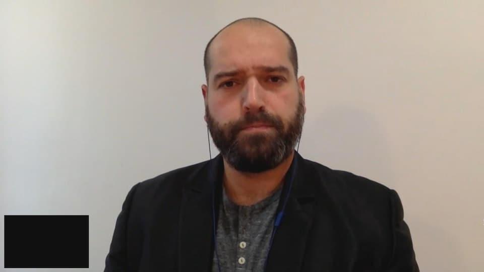 Un homme accorde une entrevue en visioconférence.