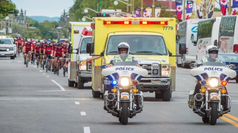 Deux motos de police suivies de deux ambulances et d'un peloton de cyclistes.
