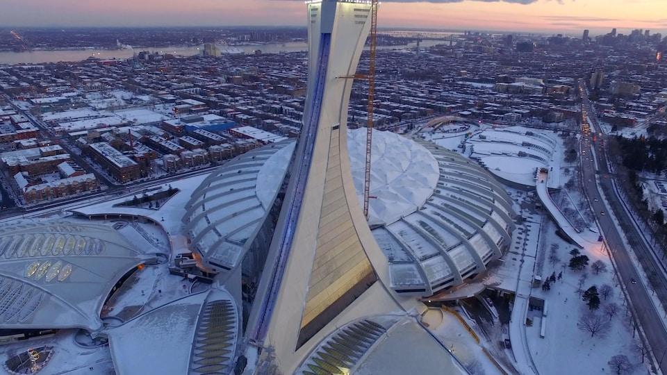 On voit le stade olympique du côté nord, de haut, en contre-plongée, l'hiver, au soleil couchant. Au loin, on aperçoit le fleuve Saint-Laurent et le centre-ville de Montréal.