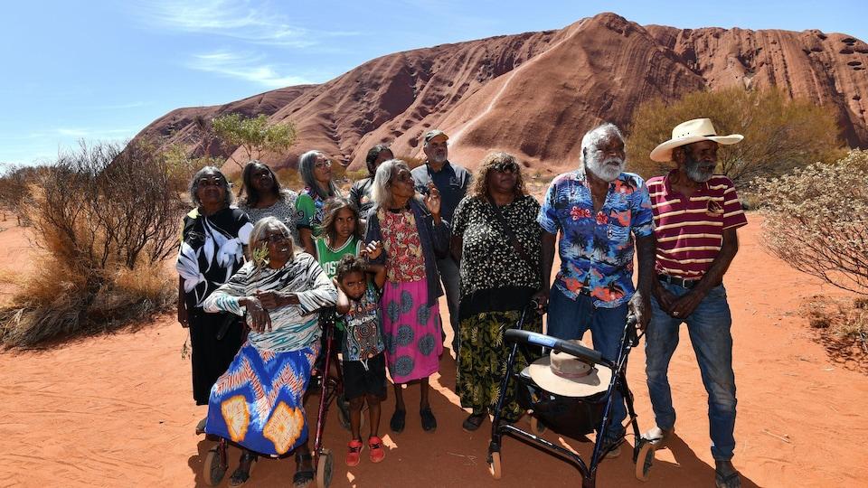 Une famille aborigène au grand complet pose devant le rocher.