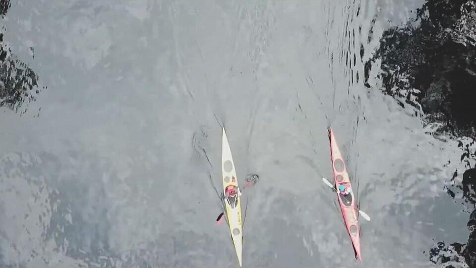 Deux kayaks naviguent sur une rivière.