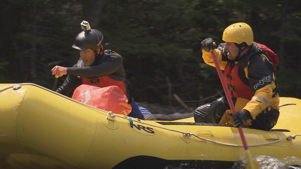 Deux hommes pagaient dans une rivière tumultueuse.