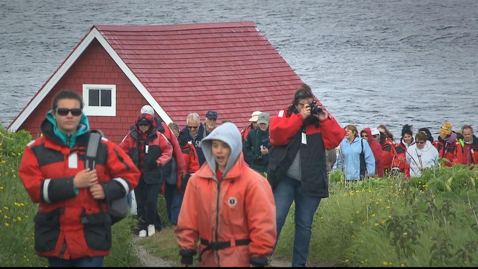 Plusieurs touristes prennent des photos et admirent le paysage de la Côte-Nord.
