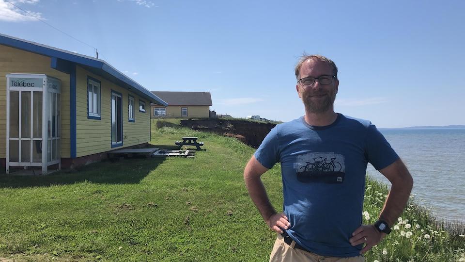 Un homme devant des bâtiments et la mer.
