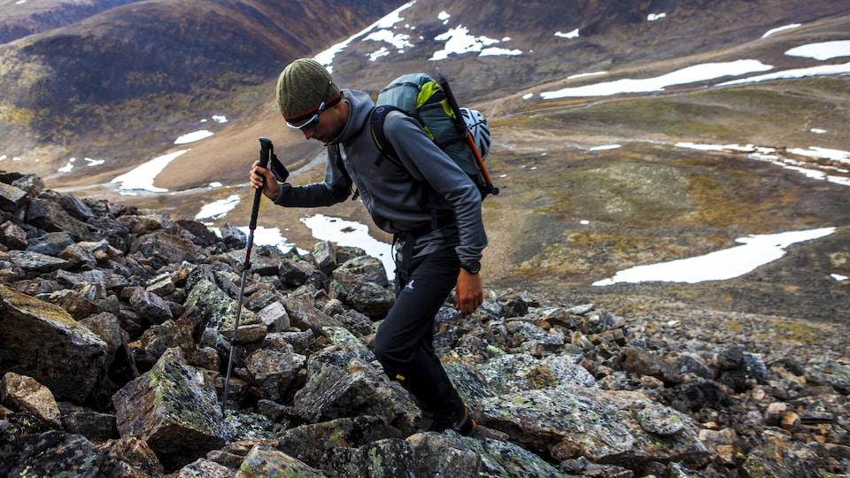 Un homme monte une montagne de roche dans le nord du Québec.