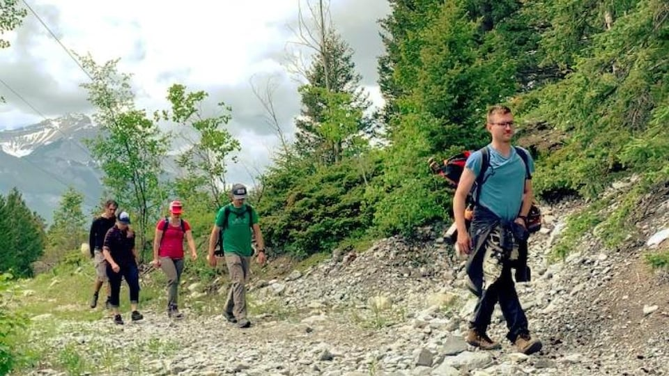 Un groupe de cinq personnes marche en montagne.