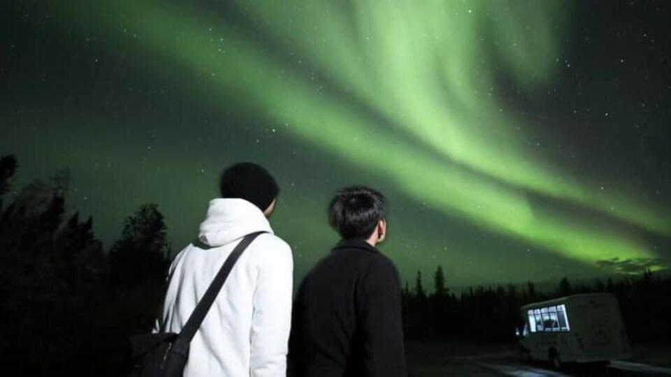 Deux personnes asiatiques observent les aurores boréales.