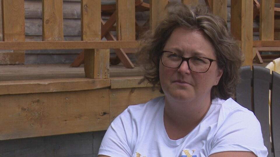 Une femme aux cheveux courts porte des lunettes rectangulaires.