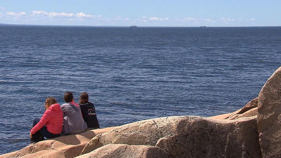Trois touristes assis sur une roche, regardent au large du fleuve Saint-Laurent, au Cap-de-Bon-Désir à Grandes-Bergeronnes