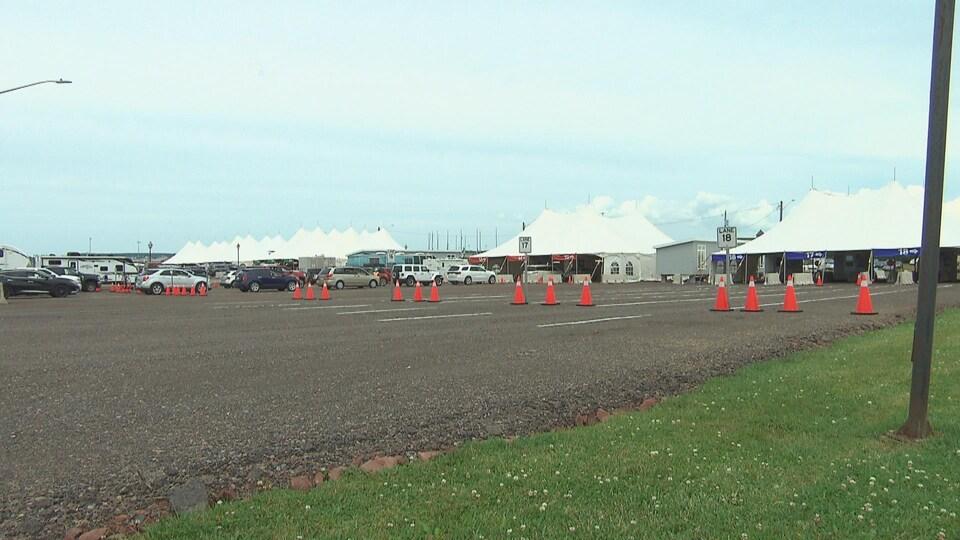 Des véhicules font la file entre des cônes de circulation, devant un chapiteau.