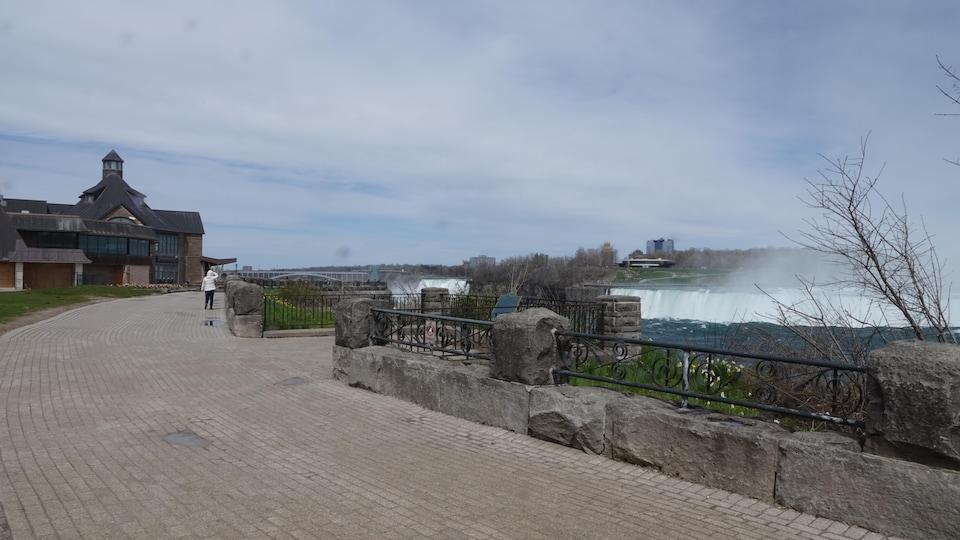 Une personne marche au loin sur le chemin en bordure des chutes Niagara. On voit les chutes derrière les clôtures.