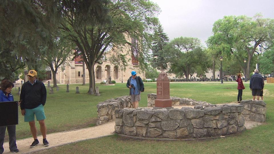 Trois personnes se situent à l'avant-plan, deux regardent un panneau indicatif de l'histoire de Louis Riel et le dernier tient un appareil photo à la main, à côté de la tombe. A l'arrière-plan à droite, à proximité de la tombe, trois autres personnes discutent. On voit la cathédrale de Saint-Boniface en arrière-plan.