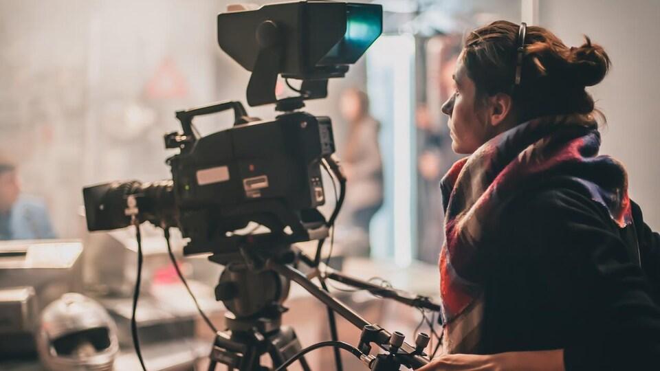 Une femme derrière une caméra.