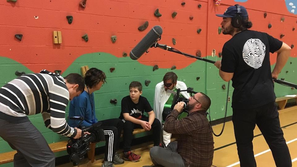 Une équipe technique et des acteurs durant le tournage dans un gymnase
