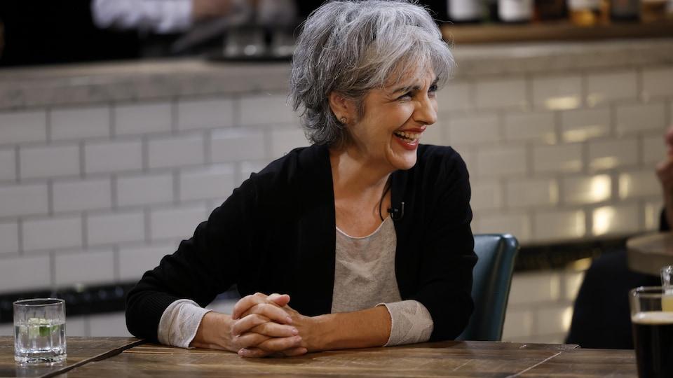 La comédienne Carole Chatel, assise à table, éclate de rire.