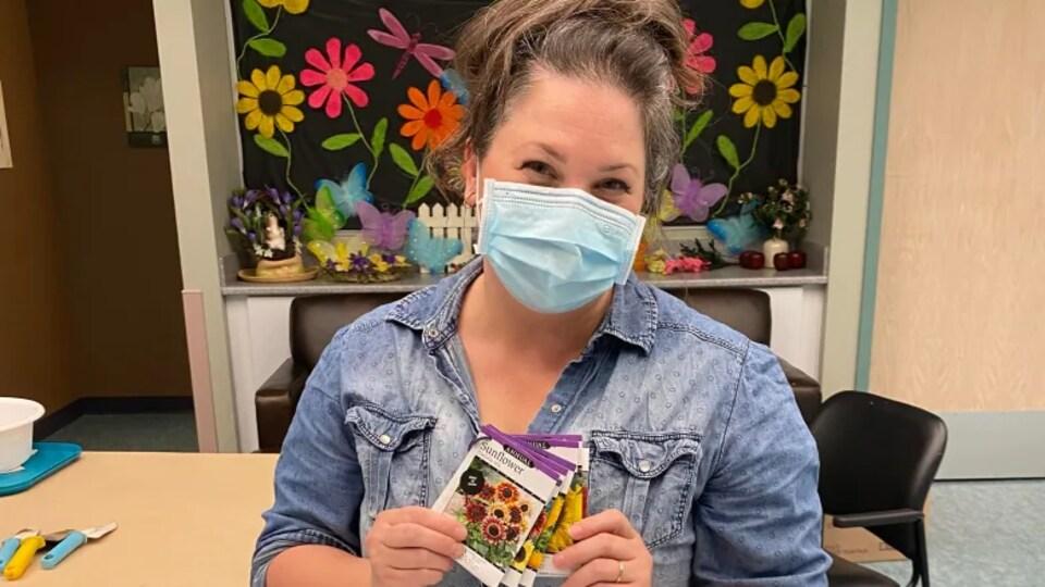 L'infirmière Susan Dyck est assise et tient dans ses mains un petit paquet de graines de tournesols.