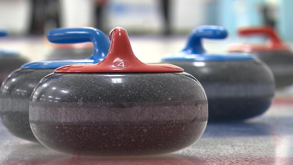 Des pierres de curlings sur la glace.