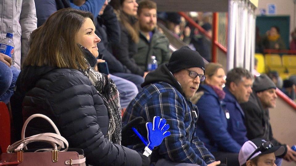Des adultes regardent un match de hockey dans les gradins d'un aréna.
