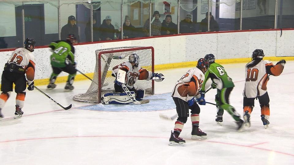 Des joueurs tentent de marquer un but dans le filet de l'équipe adverse.