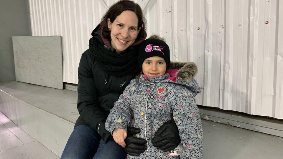 Une femme et sa fille de 5 ans sourient à la caméra.