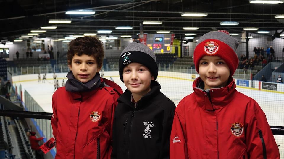 Debout dans les gradins, les trois garçons sourient à la caméra. Derrière eux, une partie est en cours sur la patinoire.