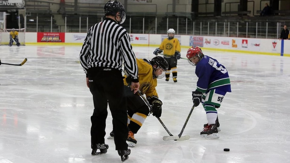 Mise au jeu au centre de la glace au Tournoi de hockey pee-wee de Jonquière.