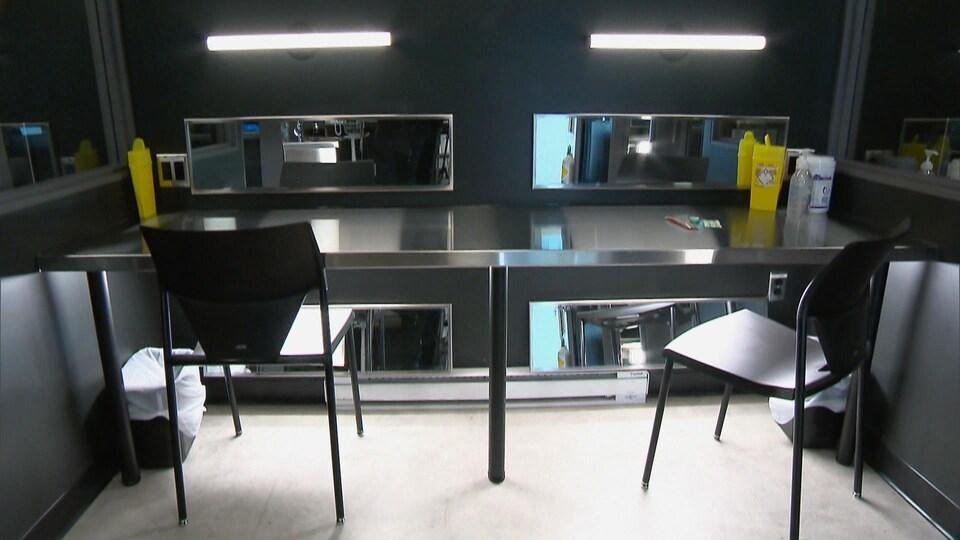 Une salle d'injection où sont disposés des seringues et des contenants à déchets sur une table stérile en aluminium.