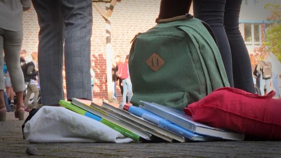 Un sac d'école et des livres déposés au sol dans une cour d'école.