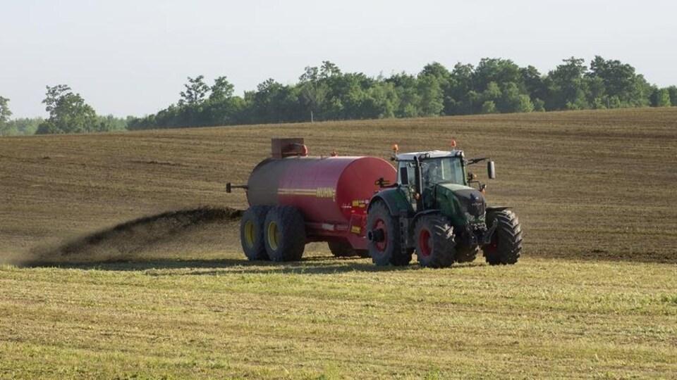 Un tracteur déverse du purin dans un champ.
