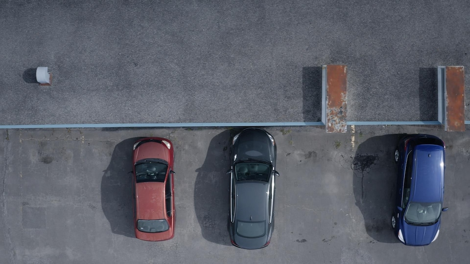 Des voitures vues de haut à l'entrée d'un motel.