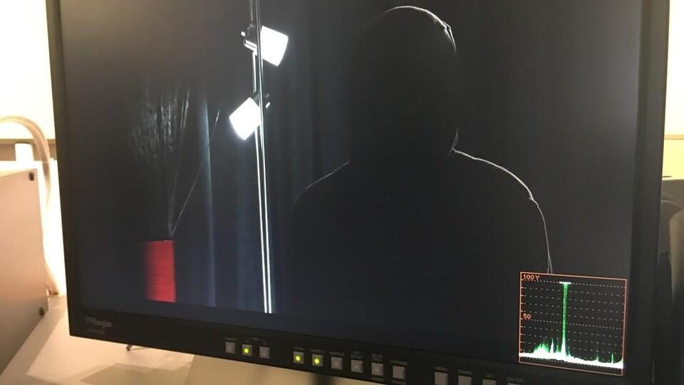 Sur un écran, on voit une personne qui témoigne de façon anonyme devant une caméra.