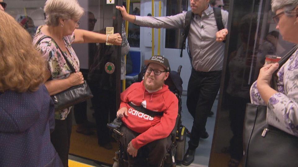 Un homme en fauteuil roulant sort d'un train.