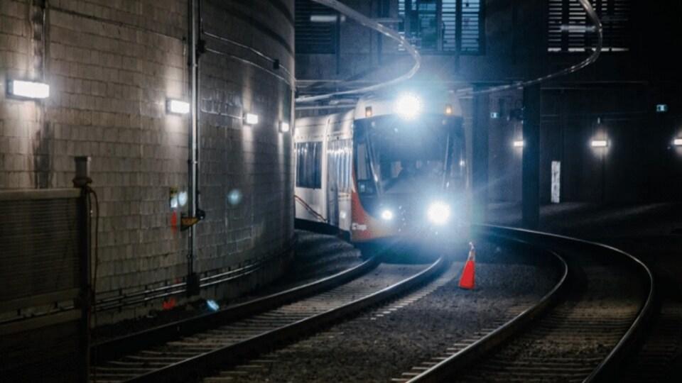 Un train léger sur rail la nuit.