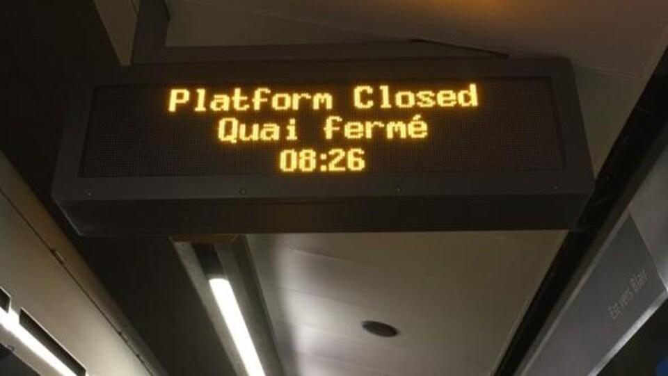 Une enseigne qui indique « quai fermé, 8 h 26 ».