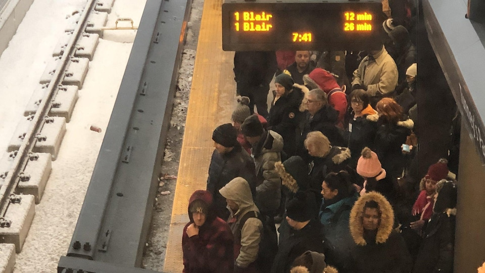 Des dizaines de personnes qui attendent près des rames.