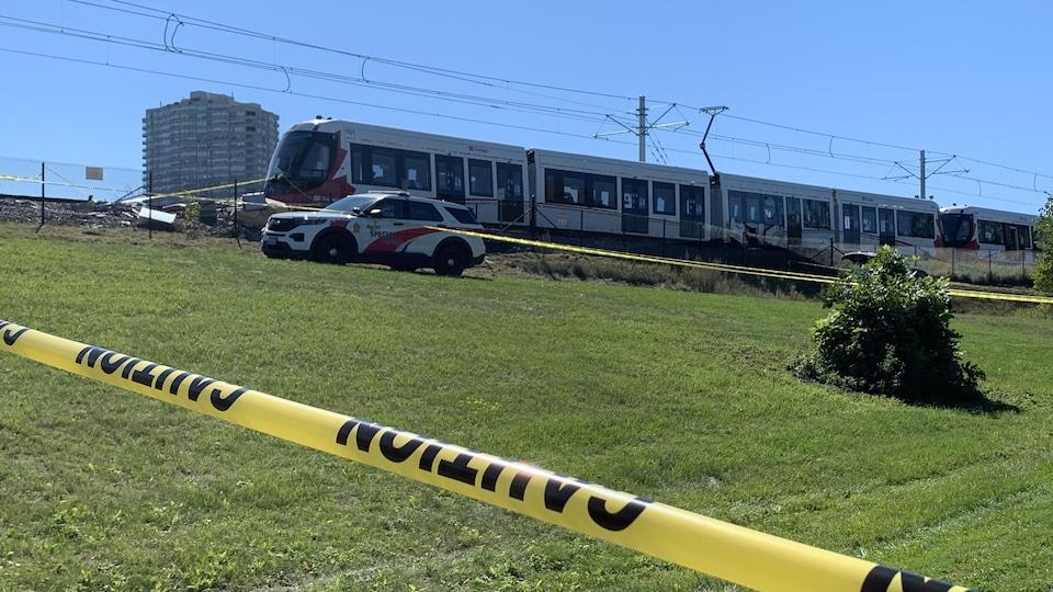 Au loin, un train qui a déraillé, une voiture de police et un périmètre de sécurité.