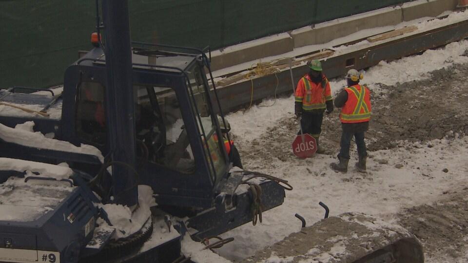 Deux ouvriers près d'un engin sur le chantier de construction