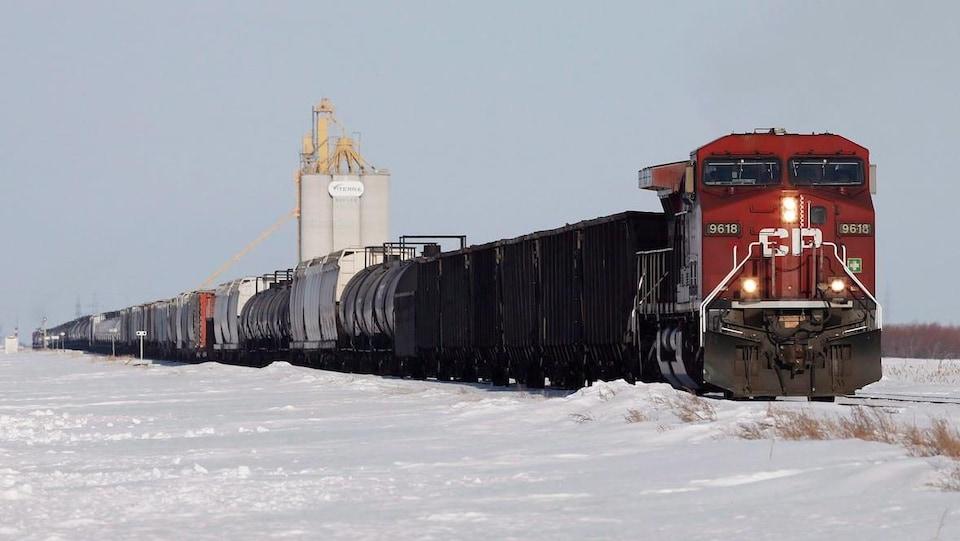 Un train de marchandises en hiver proche d'un silo de grains.