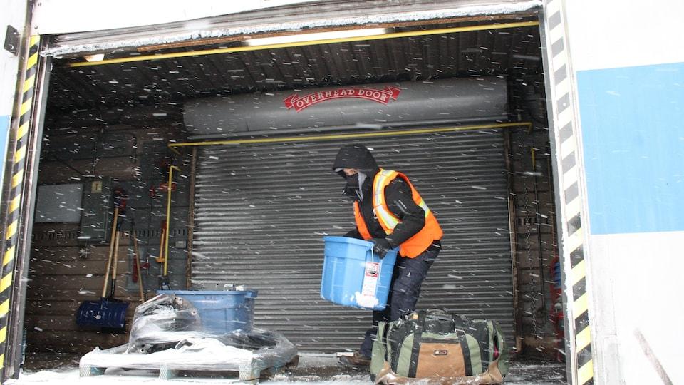 Un travailleur en veste orange soulève un bac de plastique.
