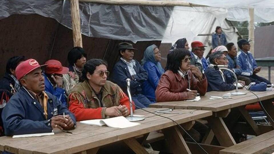 Plusieurs chefs dénés sont assis à une table.