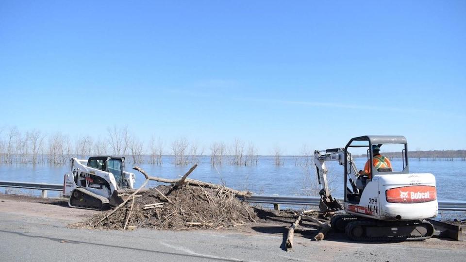 Un bélier mécanique et une excavatrice déplacent des troncs d'arbres sur la route.