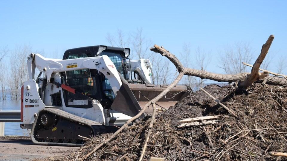 Un bélier mécanique sur la route pousse un monticule de terre, de branches d'arbres et d'autres végétaux.