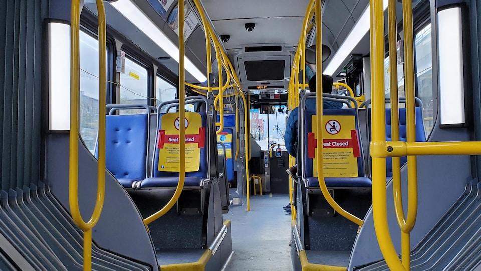 L'intérieur d'un autobus avec des affiches sur certains sièges stipulant qu'ils ne sont pas accessibles.
