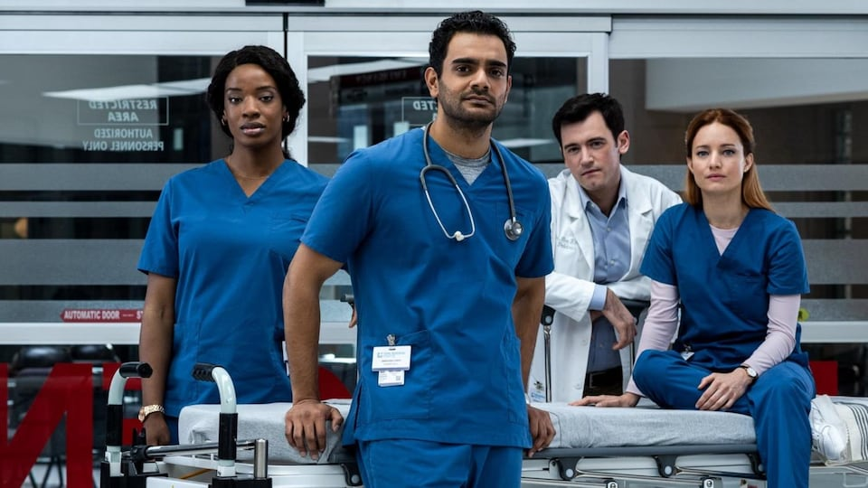 Les quatre personnes, habillées de blouses bleues, regardent la caméra.