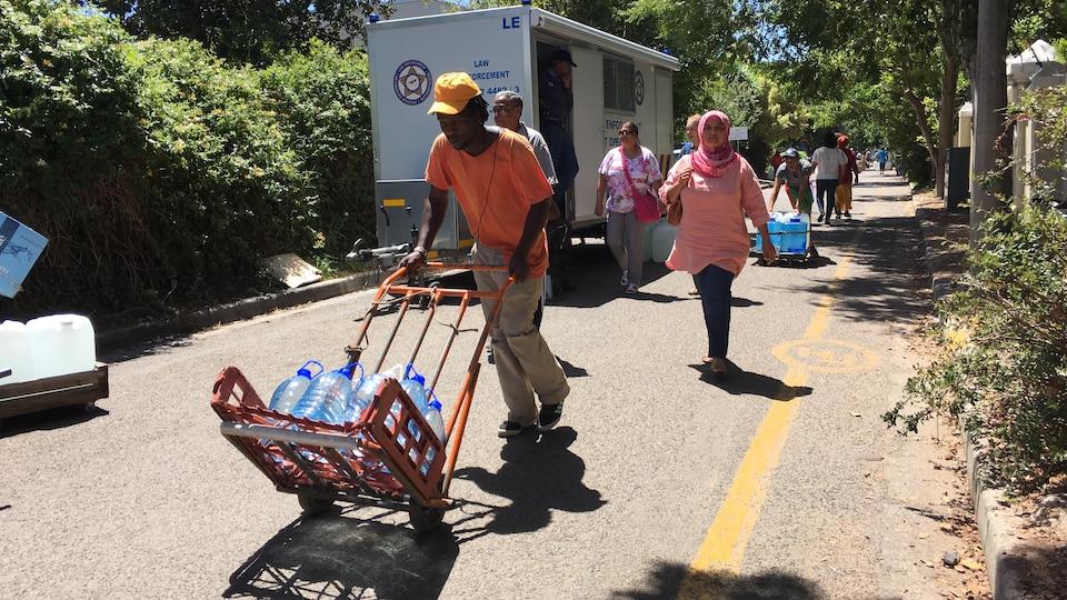 Des gens transportent des bidons d'eau dans des charriots.