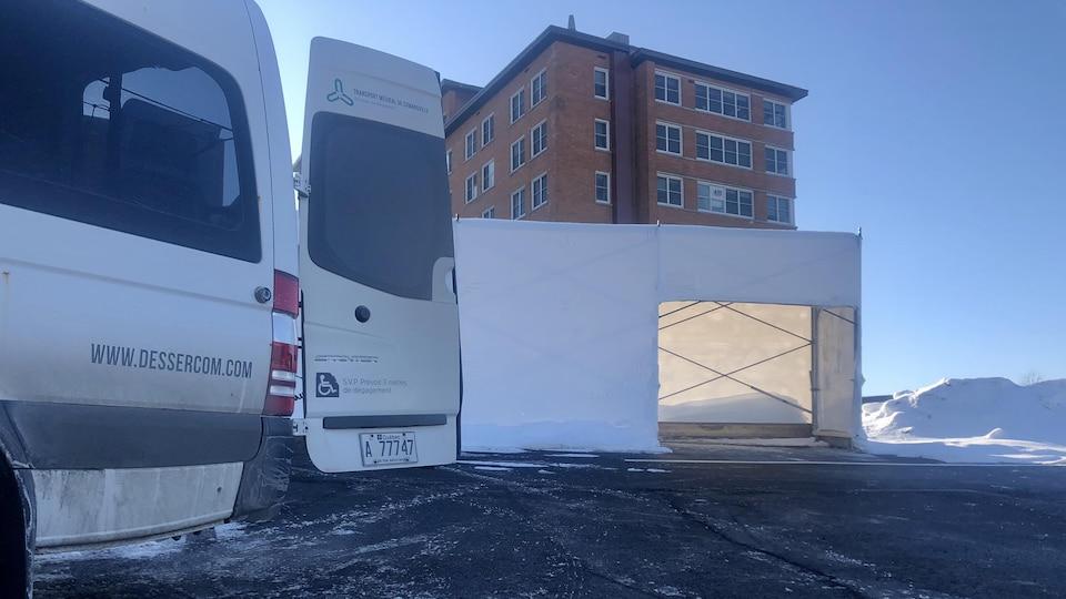 Un camion de transport médical adapté devant un hôpital.