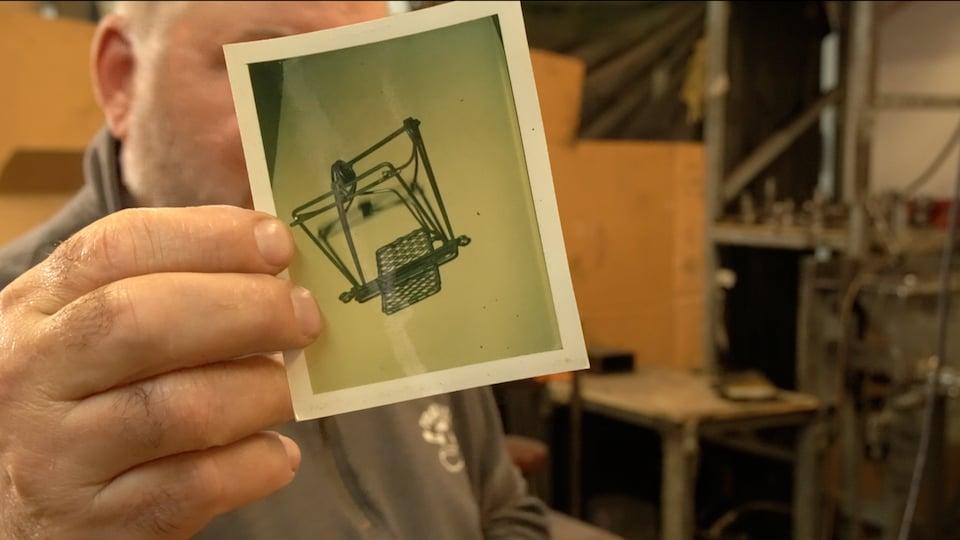 Un homme montre une photo d'une création de son père.