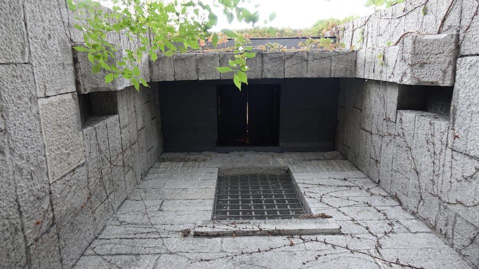 Un mur de pierre en haut duquel une trappe laisse passer un filet de lumière.