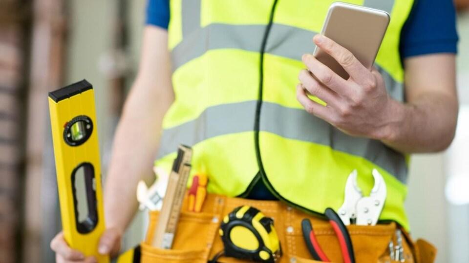 Un travailleur de la construction consulte son téléphone intelligent.