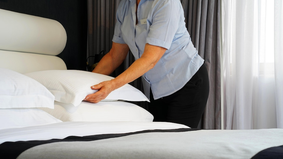 Une femme de ménage dépose un oreiller sur un lit fraîchement fait. Nous ne pouvons voir le visage de la dame.